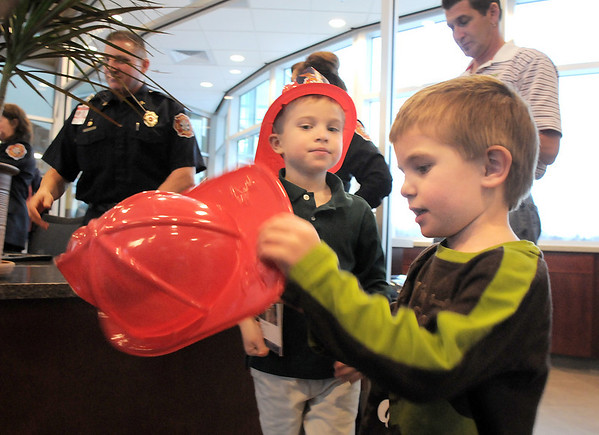 Michael Lee Kastner, 6, left, and his brother Nicholan, 4, try on their  plastic fire hats during the public open house of the new North Metro Fire Rescue District administration building on Thursday.<br /> <br /> January 20, 2011<br /> staff photo/David R. Jennings