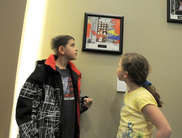 Elias Turner, 10, left, shows his sister Harmoni Garneau, 9, his painting given the Chief's Award during the public open house of the new North Metro Fire Rescue District administration building on Thursday.<br /> <br /> January 20, 2011<br /> staff photo/David R. Jennings