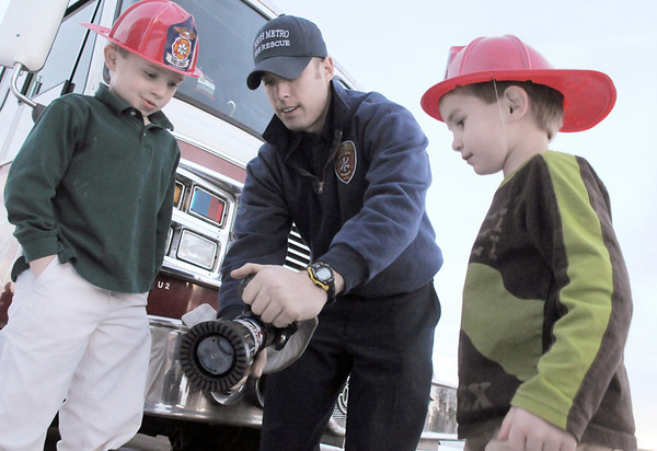 Firefighter/paramedic Rob Perry, center, shows Michael Lee Kastner, 6, left, and his brother Nicholan, 4, how a fire nozzle works during the public open house of the new North Metro Fire Rescue District administration building on Thursday.<br /> <br /> January 20, 2011<br /> staff photo/David R. Jennings