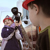 Kayliana Schild, 6, holds a fire hose from an fire engine while Nicholan Kastner, 4, watches  during the public open house of the new North Metro Fire Rescue District administration building on Thursday.<br /> <br /> January 20, 2011<br /> staff photo/David R. Jennings
