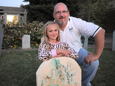 """Emma O'Dell, 9, poses with her father Jim, at the Molly Brown grave stone in the front yard of thier Halloween decorated home dubbed """" The Chilling Hour""""  at 920 Coral St. on Wednesday.  Emma will be a vampire for the haunted house. October 19, 2011 staff photo/ David R. Jennings"""