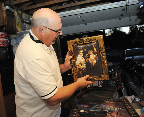 "Jim O'Dell looks at a scary painting for his Halloween haunted house dubbed "" The Chilling Hour""  at 920 Coral St. on Wednesday.  O'Dell's garage will be transformed into a room of the haunted house.<br /> October 19, 2011<br /> staff photo/ David R. Jennings"