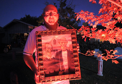 """Jim O'Dell holds a scary picture for the Halloween decorations, transforming his home into his haunted house dubbed """" The Chilling Hour""""  at 920 Coral St. on Wednesday.   October 19, 2011 staff photo/ David R. Jennings"""