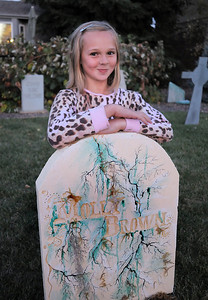 """Emma O'Dell, 9, poses at the Molly Brown grave stone in the front yard of her Halloween decorated home dubbed """" The Chilling Hour""""  at 920 Coral St. on Wednesday.  Emma will be a vampire for the haunted house. October 19, 2011 staff photo/ David R. Jennings"""
