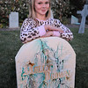 "Emma O'Dell, 9, poses at the Molly Brown grave stone in the front yard of her Halloween decorated home dubbed "" The Chilling Hour""  at 920 Coral St. on Wednesday.  Emma will be a vampire for the haunted house.<br /> October 19, 2011<br /> staff photo/ David R. Jennings"