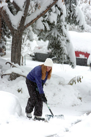 BE1101SNO14<br /> Laura Hoyle shovels a neighbor's sidewalk on Thursday in Lac Amora. <br /> <br /> October 29, 2009<br /> Staff photo/David R. Jennings