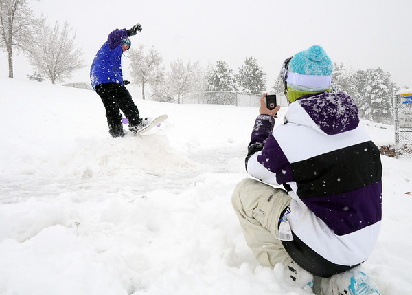 Lance Kittel, 16, right, photographs Aaron Corbet, 16, while snowboarding down a slope at Community Park  on Wednesday. Boulder Valley Schools were closed Wednesday due to the wniter storm.<br /> October 28, 2009<br /> Staff photo/David R. Jennings