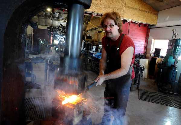 METALWORKER04<br /> David Norrie uses a pneumatic forging hammer, which was made in 1929, to shape steel at his studio in Berthoud.<br /> <br /> Photo by Marty Caivano/Camera/Dec. 30, 2009
