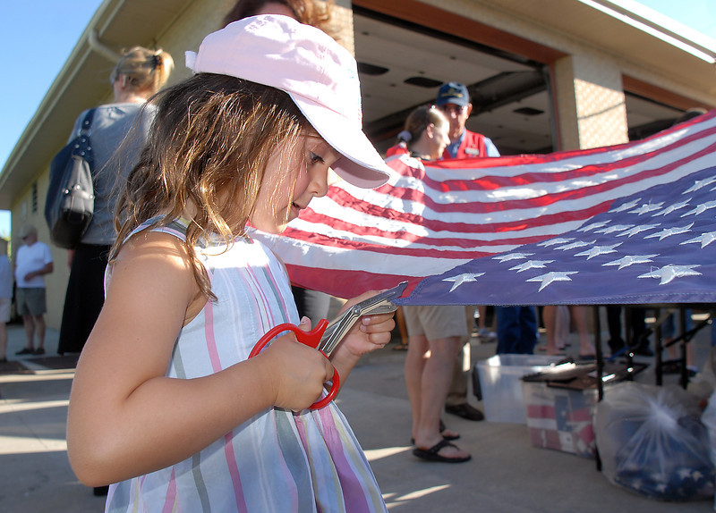 Kate Aldworth, 5, begins to cut the field of stars on a flag during the flag retirement ceremony at North Metro Fire station 61 on Tuesday.<br /> June 14, 2011<br /> staff photo/David R. Jennings