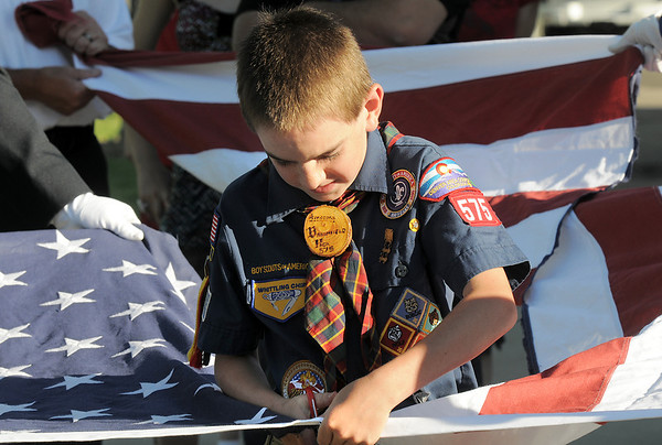 Cub Scout James Hall, 9, cuts the field of stars from a flag during the flag retirement ceremony at North Metro Fire station 61 on Tuesday.<br /> June 14, 2011<br /> staff photo/David R. Jennings