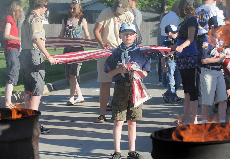 Cub Scout Evan Beard, 8, holds the strips of a flag for firefighters to place into the fires during the flag retirement ceremony at North Metro Fire station 61 on Tuesday.<br /> June 14, 2011<br /> staff photo/David R. Jennings