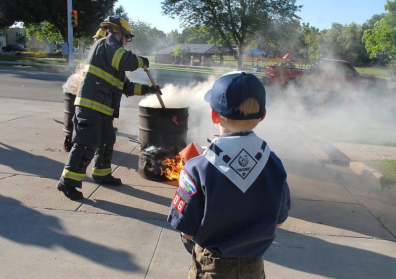 Cub Scout Evan Beard, 8, watches North Metro Fire firefighters tend the fires of burning flags during the flag retirement ceremony at North Metro Fire station 61 on Tuesday.<br /> June 14, 2011<br /> staff photo/David R. Jennings
