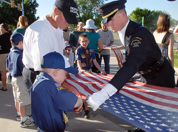 Cub Scout Aiden Dahlbach, 8, left, cuts the stars from a flag with the help of his father Broomfield Police officer Todd Dahlbach, right, and officer David Walts during the flag retirement ceremony at North Metro Fire station 61 on Tuesday.<br /> June 14, 2011<br /> staff photo/David R. Jennings