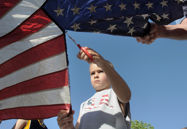Ryan Messmer, 7, cuts the field of stars from a flag during the flag retirement ceremony at North Metro Fire station 61 on Tuesday.<br /> June 14, 2011<br /> staff photo/David R. Jennings