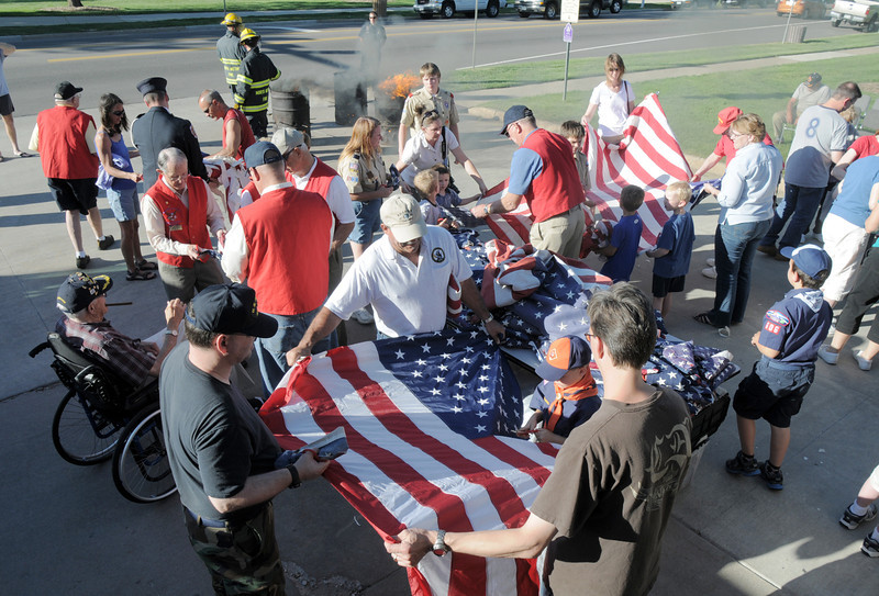 Members of the community, Broomfield Veterans Memorial Museum, North Metro Fire and Broomfeild Police cut the stars from flags before they are retired by being burned during the flag retirement ceremony at North Metro Fire station 61 on Tuesday.<br /> June 14, 2011<br /> staff photo/David R. Jennings