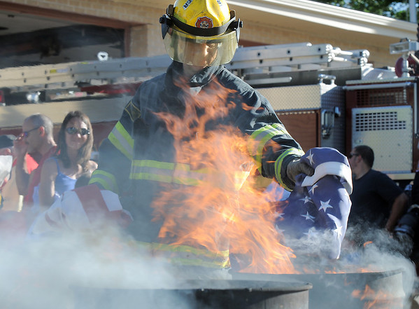 Firefighter Brian Thorngate places a flag's field of stars into a burning barrel during the flag retirement ceremony at North Metro Fire station 61 on Tuesday.<br /> June 14, 2011<br /> staff photo/David R. Jennings
