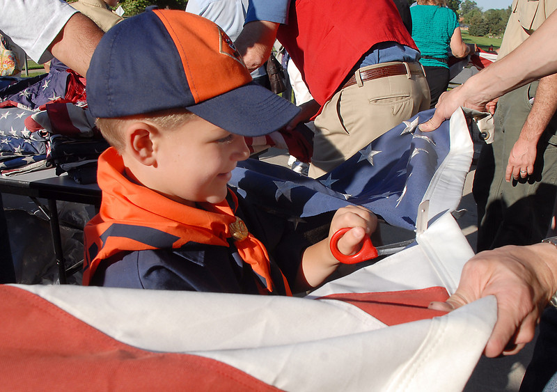 Cub Scout Austin Stuart, 6, helps cut away the stars from a flag during the flag retirement ceremony at North Metro Fire station 61 on Tuesday.<br /> June 14, 2011<br /> staff photo/David R. Jennings