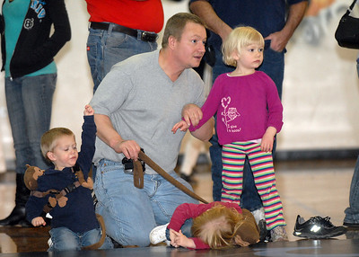 Harold Trudeau watches matches with his children Ian, 2, right, Ivy, 2, and Lily, 4, during the Old Timers Wrestling tournament on Saturday at Broomfield High School.   March 13, 2010 Staff photo/David R. Jennings