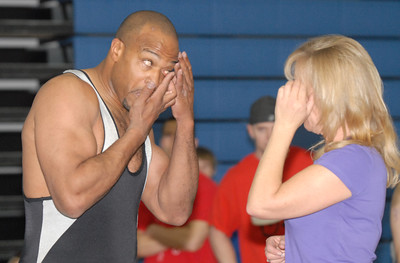 Dewaine Jones, 42, puts a contact in his eye with help from his wife Libby during the Old Timers Wrestling tournament on Saturday at Broomfield High School.   March 13, 2010 Staff photo/David R. Jennings