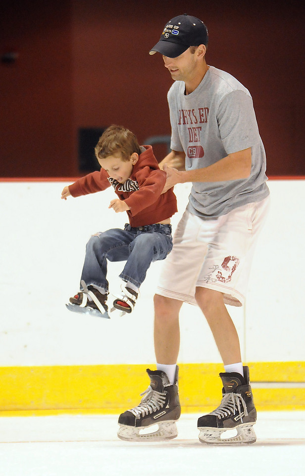 Tommy Ruffles, 4, his carried by his father Tom while skating during Wednesday's free ice skating at the 1stBank Center.<br /> <br /> September 15, 2010<br /> staff photo/David R. Jennings