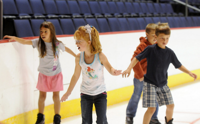 Laney Bowers, 5, center, skates with Paige Rodgers, 7, left, Trenton Bowers, 7, and Bryce Rodgers, 7, during Wednesday's free ice skating at the 1stBank Center.<br /> <br /> September 15, 2010<br /> staff photo/David R. Jennings