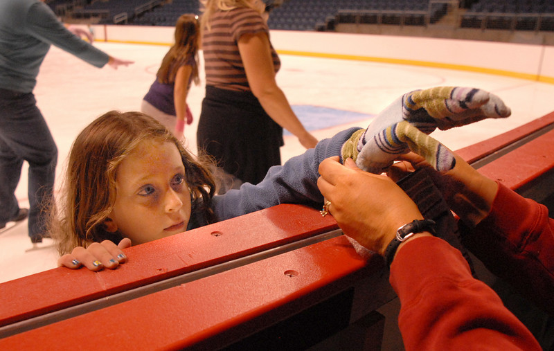 Jolene Jacobi, 6, get gloves from her mother while skating during Wednesday's free ice skating at the 1stBank Center.<br /> <br /> September 15, 2010<br /> staff photo/David R. Jennings