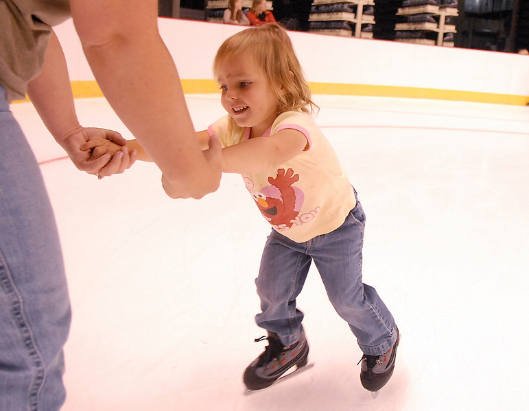 Keira Disch, 3, holds on to her mothers hands while skating during Wednesday's free ice skating at the 1stBank Center.<br /> <br /> September 15, 2010<br /> staff photo/David R. Jennings