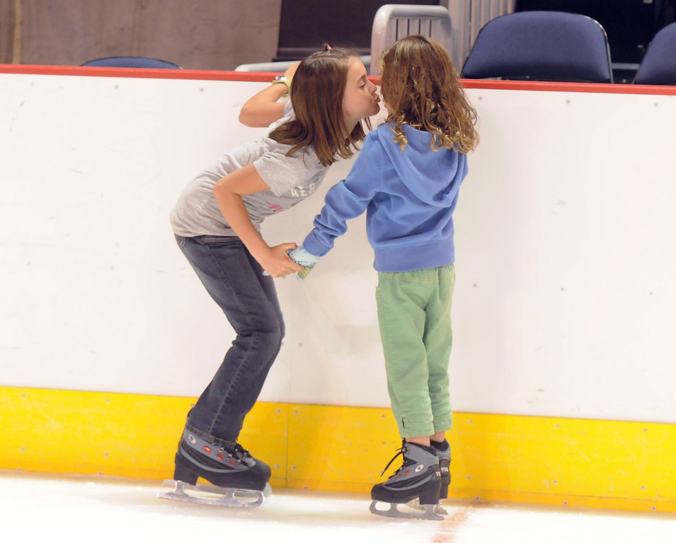 Adriana Jacobi, 9, left, gives her sister Jolene, 6, a kiss while skating during Wednesday's free ice skating at the 1stBank Center.<br /> <br /> September 15, 2010<br /> staff photo/David R. Jennings