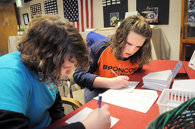 Hulstrom Options School students Jeni Robinson, 12, left, and Madison Allen, 13, address holiday card envelopes for soldiers and veterans during the open house at the Broomfield Veterans Memorial Museum on Saturday. January 14, 2012 staff photo/ David R. Jennings