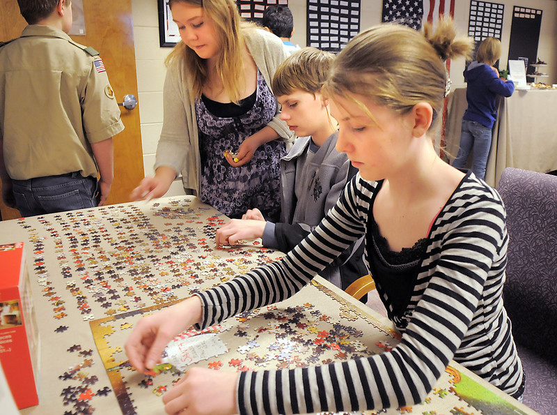 Hulstrom Options School students Elizabeth Platt, 12, right, her brother William, 13, and Abi Dancho, 12, work on a jigsaw puzzle during the open house at the Broomfield Veterans Memorial Museum on Saturday.<br /> January 14, 2012<br /> staff photo/ David R. Jennings