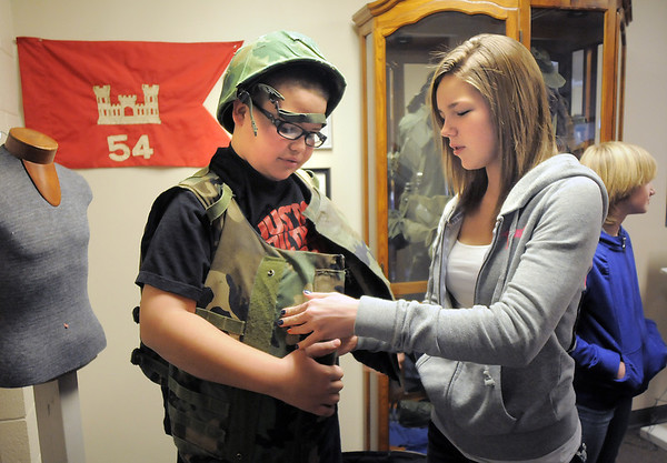 Hulstrom Options School students Makenzie Wolz, 13, right, looks at the Vietman era flak jacket worn by Antonio Teran, 12, left,  during the open house at the Broomfield Veterans Memorial Museum on Saturday.<br /> January 14, 2012<br /> staff photo/ David R. Jennings