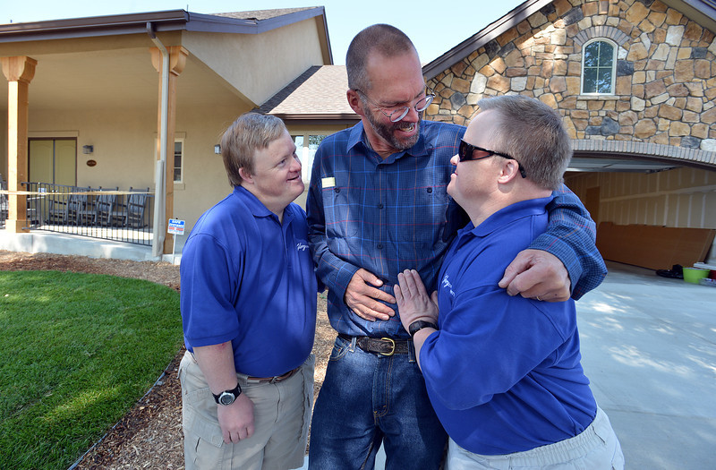 Mike Hembd, left, and his twin brother Mark, right, 43, greet Pastor John Hess of the First Presbyterian Church of Boulder at the open house on Saturday for Glory Community, a private nonprofit, residential home for adults with intellectual disabilities. The Hembd's will be living in the house starting October 1st with six other residents.<br /> September 21, 2012<br /> staff photo/ David R. Jennings