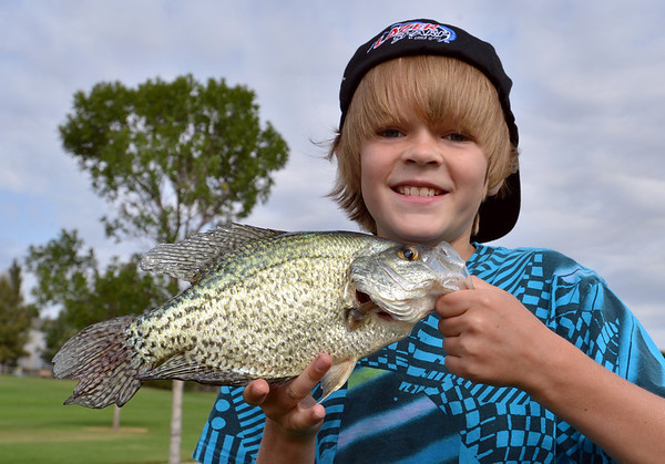Joel Kressen, 11, poses with a large fish he caught before releasing the fish back to the water during the Optimists Club Fishing Derby on Saturday at the Trails Park.<br /> August 25, 2012<br /> staff photo/ David R. Jennings