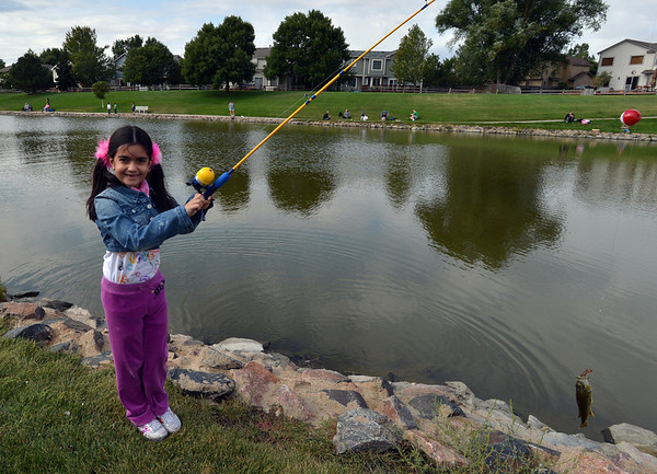 Lujane Yacoub, 7, shows a fish she just caught during the Optimists Club Fishing Derby on Saturday at the Trails Park.<br /> August 25, 2012<br /> staff photo/ David R. Jennings
