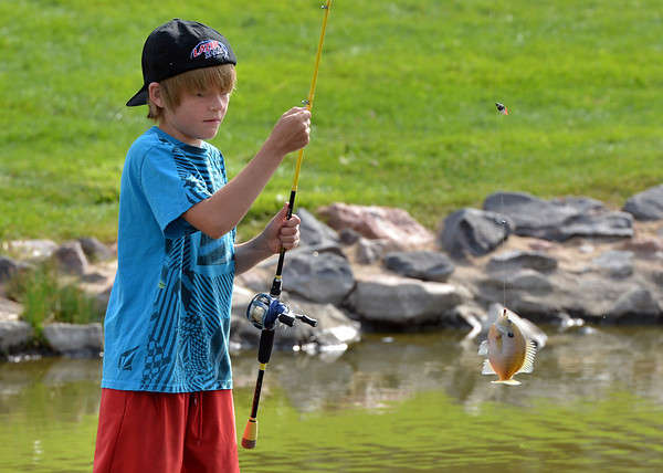 Joel Kressen 11, reels in a fish he caught during the Optimists Club Fishing Derby on Saturday at the Trails Park.<br /> August 25, 2012<br /> staff photo/ David R. Jennings