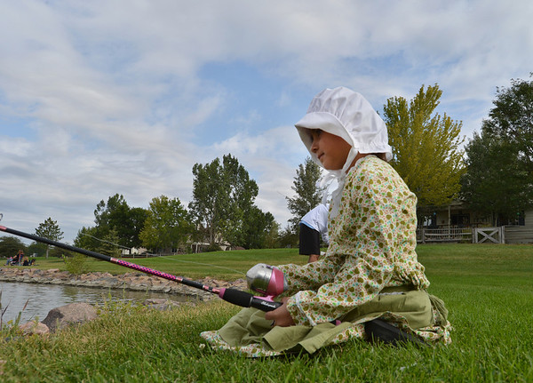 Payton Delier, 7, left, dressed in a Becky Thatcher outfit,  fishes during the Optimists Club Fishing Derby on Saturday at the Trails Park.<br /> August 25, 2012<br /> staff photo/ David R. Jennings