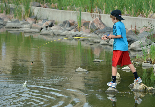 Joel Kressen, 11, reels in a large fish he caught during the Optimists Club Fishing Derby on Saturday at the Trails Park.<br /> August 25, 2012<br /> staff photo/ David R. Jennings