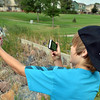 Joel Kressen, 11, takes a picture of a fish he caught during the Optimists Club Fishing Derby on Saturday at the Trails Park.<br /> August 25, 2012<br /> staff photo/ David R. Jennings