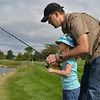 Ben Tarr helps his daughter Aubrey, 4, with her fishing pole during the Optimists Club Fishing Derby on Saturday at the Trails Park.<br /> August 25, 2012<br /> staff photo/ David R. Jennings