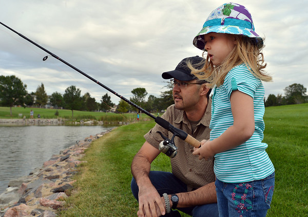 Aubrey Tarr, 4, fishes with her father Ben during the Optimists Club Fishing Derby on Saturday at the Trails Park.<br /> August 25, 2012<br /> staff photo/ David R. Jennings