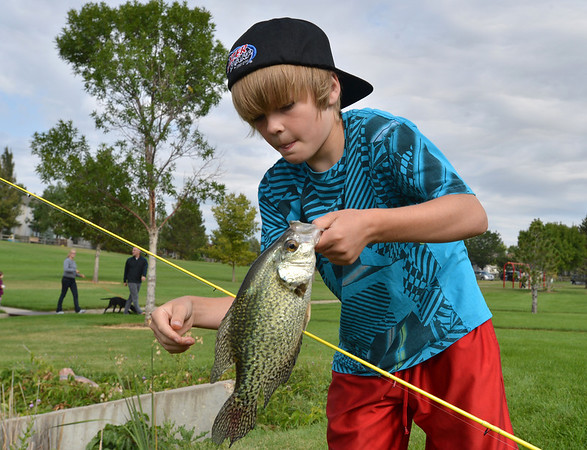 Joel Kressen, 11, takes a large fish off of his line he caught during the Optimists Club Fishing Derby on Saturday at the Trails Park.<br /> August 25, 2012<br /> staff photo/ David R. Jennings