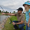 Ben Tarr points to where his daughter, Aubrey, 6, should look when fishing during the Optimists Club Fishing Derby on Saturday at the Trails Park.<br /> August 25, 2012<br /> staff photo/ David R. Jennings