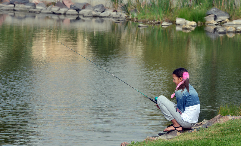 Emiko Boyer, 11, waits for a fish to bite during the Optimists Club Fishing Derby on Saturday at the Trails Park.<br /> August 25, 2012<br /> staff photo/ David R. Jennings