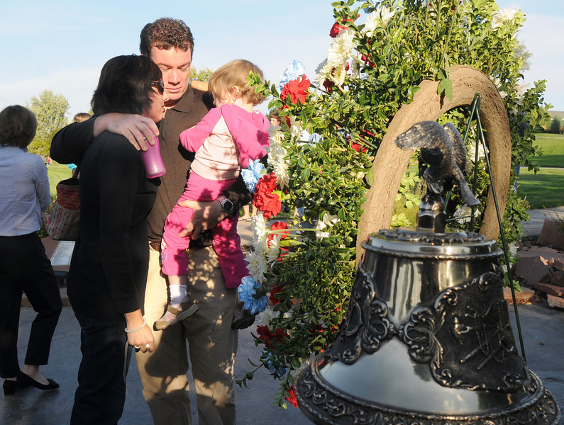 Taking a moment to remember his brother, Michael Faughnan, center, holding his daughter Ava, 2, with sister-in-law Cathy Faughnan, widow of Chris Faughnan who died in the World Trade Center, after the ceremony at the 9/11 Memorial in Community Park in Broomfield.<br /> <br /> <br /> Sept. 11, 2009<br /> Staff photo/David R. Jennings