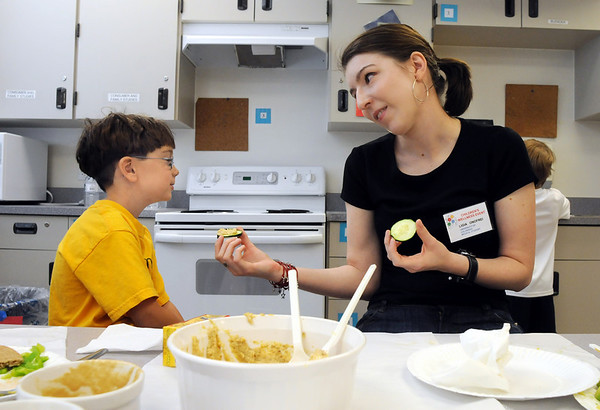 CU medical student Ligia Onofrei, right, tries to convince Owen Meyers, 6, to eat a snappy summer snack  during the Broomfield Trail Adventure and Children's Wellness event at Aspen Creek School.<br /> June 6, 2009<br /> staff photo/David Jennings