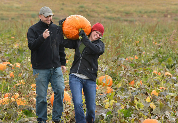 Darcie Eggy carries a pumpkin ,with the encouragement of her friend Josh Ramsey, from a field at the Rock Creek Farm on Saturday.<br /> October 6, 2012<br /> staff photo/ David R. Jennings