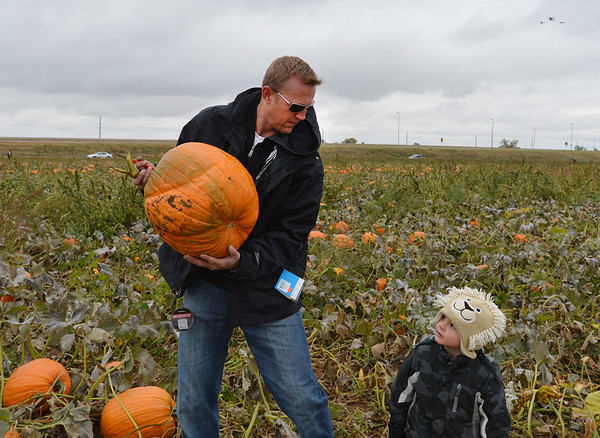Adam George, left, and his son Will, 3, carries a pumpkin from a field at the Rock Creek Farm on Saturday.<br /> October 6, 2012<br /> staff photo/ David R. Jennings