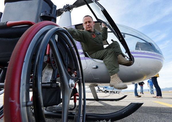 Stewart McQuillan with TYJ Global,  climbs out of a helicopter after demonstrating the Heli Leg on Thursday at TYJ Global at Rocky Mountain Metropolitan Airport. The Heli Leg is a device that McQuillan developed which allows a paraplegic pilot to fly  a helicopter. <br /> November 1, 2012<br /> staff photo/ David R. Jennings