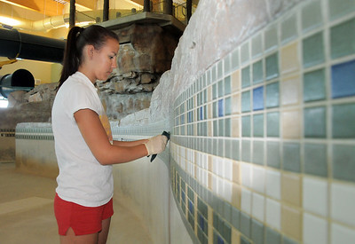 Lifeguard Megan Claussen hand scrubs the tiles on the pool during the deep cleaning of the Paul Derda Recreation Center  on Thursday. August 24, 2011 staff photo/ David R. Jennings
