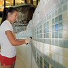 Lifeguard Megan Claussen hand scrubs the tiles on the pool during the deep cleaning of the Paul Derda Recreation Center  on Thursday.<br /> August 24, 2011<br /> staff photo/ David R. Jennings